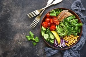 Lunch bowl with vegetables, beans and chicken meat on a dark slate, stone or metal background.